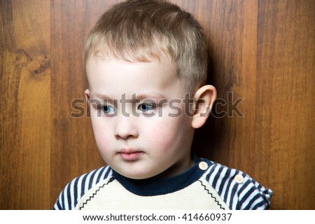 a sad  young caucasian boy. looking away