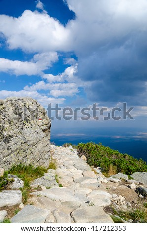 A scenic view from a high mountain stony hiker path with a tourist red sign marking on a large boulder and dwarf pines on thunderstorm clouds down in the valley and sunny blue sky above.