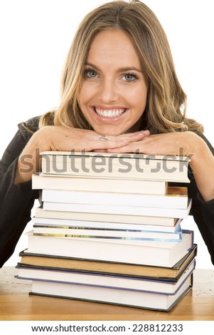 A school girl with her hands and chin on top of a stack of books.