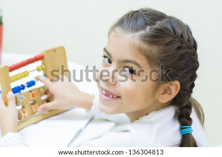 A schoolgirl at her desk with abacus