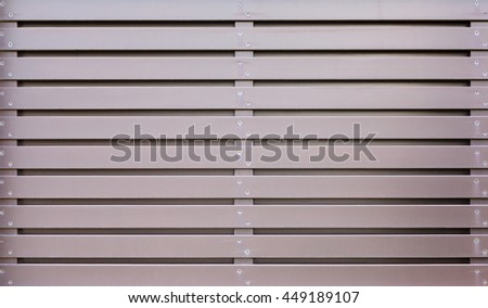 A section of brown, vertical, overlapped wooden garden fence in closeup in the sun with shadows