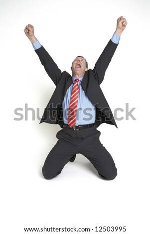 A senior businessman drops to his knees and throws his hands in the air in celebration.