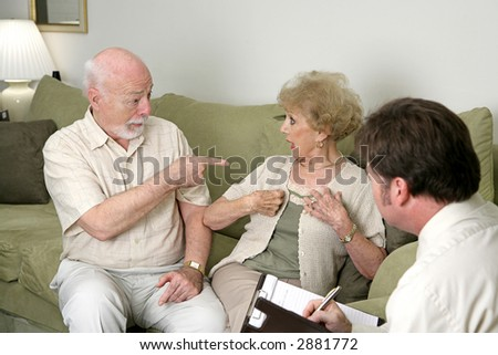 A senior couple seeking marriage counseling.  He's pointing at her and she's looking surprised.  Focus on husband.