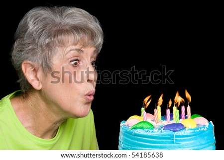 A senior female blows out candels on a cake.  Ideal for birthday, anniversary or any other celebration inference.