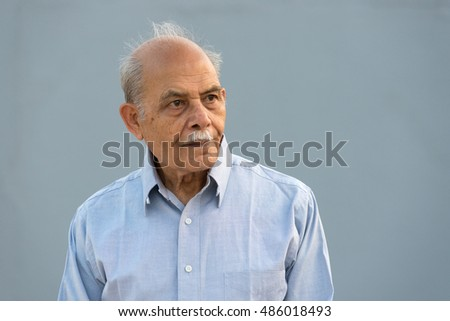 A senior Indian / South Asian man against a light blue background looking away