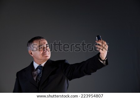 A senior manager using successfully his inseparable smartphone agenda and calendar, now taking a selfie