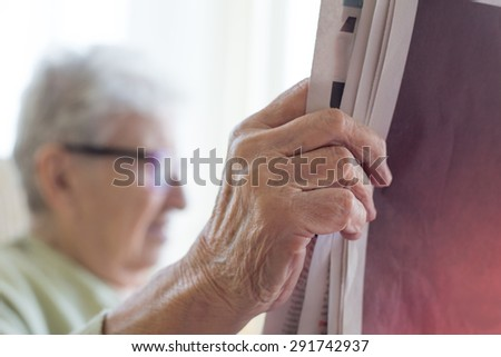 a senior person reading newspaper