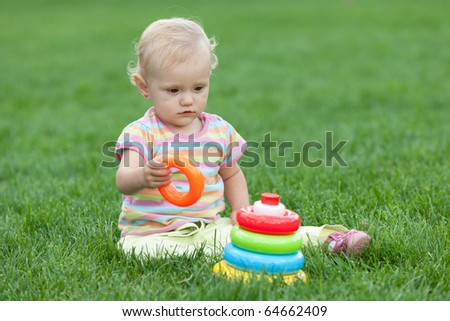 A serious little girl is playing with toys on the grass