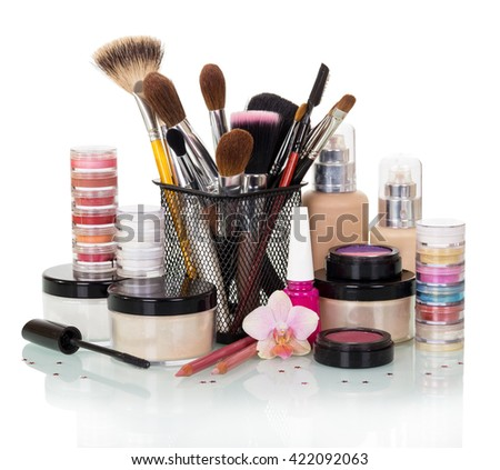 A set of brushes and makeup: eye shadow, blush, foundation, nail polish and cream isolated on white background.