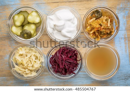 a set of fermented food great for gut health - top view of glass bowls against grunge wood:  cucumber pickles,  coconut milk yogurt, kimchi, sauerkraut, red beets, apple cider vinegar
