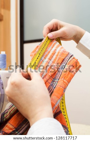 A sewer measuring a garment.
