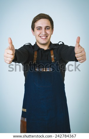 A shoot of young caucasian men in apron as a barmen. Showing the sign good, thumbs up.