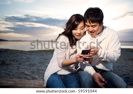 A shot of an asian couple on the phone reading text messages
