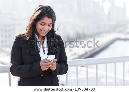 A shot of an Indian businesswoman texting on the phone  outdoor
