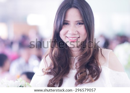 A shot of smiling confident Asian Thai woman in party