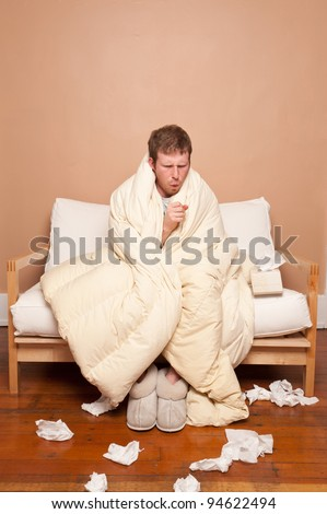 A sick man on the couch coughing