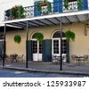 A Sidewalk Cafe And Balcony In The New Orleans French Quarter - stock photo