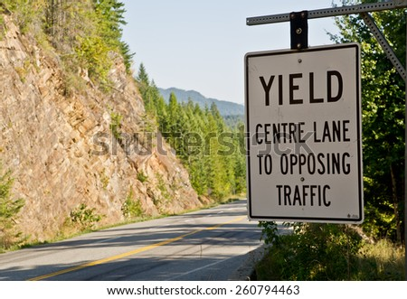 A sign alongside the road cautions travelers about  yielding the center lane to oncoming traffic