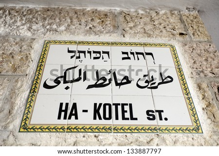 "A sign in Hebrew, Arabic and English depicting a street name in the old city of Jerusalem, Israel. The street's name is ""HaKotel"" is in Hebrew name of the holy Western Wall (aka Wailing Wall)."