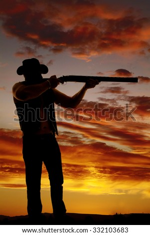 A silhouette of a cowboy getting ready to shoot his shotgun.