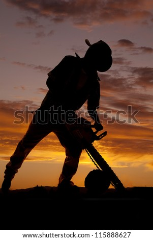 A silhouette of a cowboy using his saw to cut a log.
