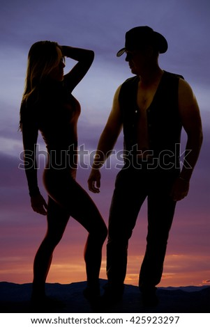 A silhouette of a woman and her cowboy standing close together.