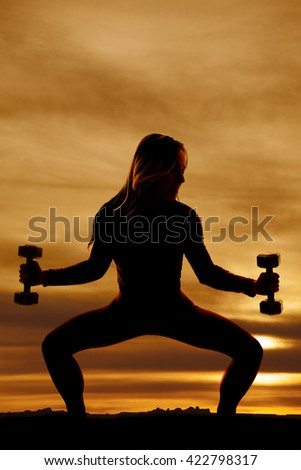 a silhouette of a woman doing a squat holding out her weights.