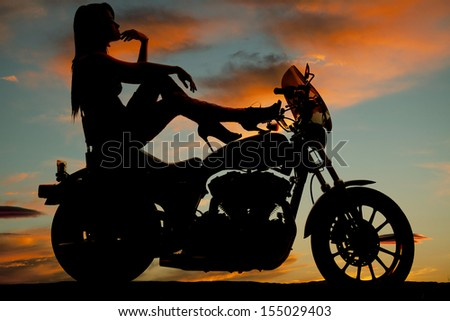 A silhouette of a woman sitting on her bike relaxing and looking out to the sky