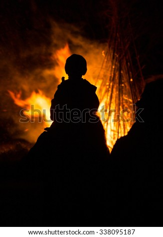 A silhouette with a fire background