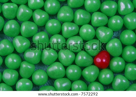 A single red candy in a cluster of green candy.