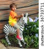 A skeptical two-year old riding a model zebra. - stock photo