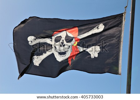 A skull and cross bones pirate flag waving in the wind.