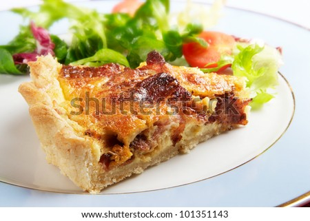 A slice of bacon and cheese quiche lorraine on a blue plate with crisp leafy salad dressing