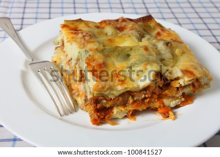 A slice of lasagne verde (spinach lasagna) on a plate with a fork, seen closeup