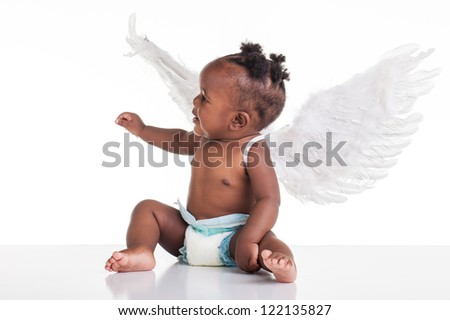 A small African baby with her angel wings on the back and a nappy on.