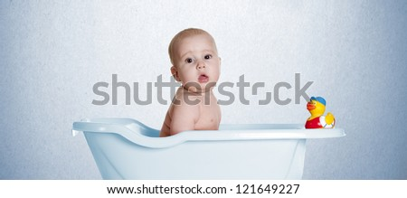 a small baby, playing in a bath with her duckling