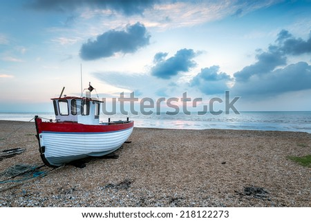 A small boat on the beach at sunrise