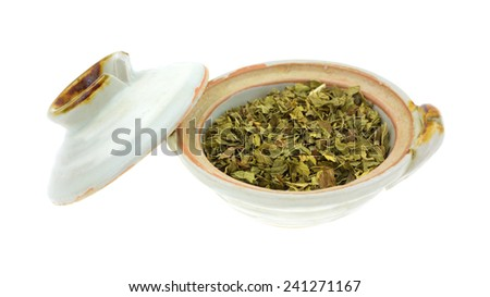 A small bowl of freshly crushed spearmint herb with the lid to the side on a white background.