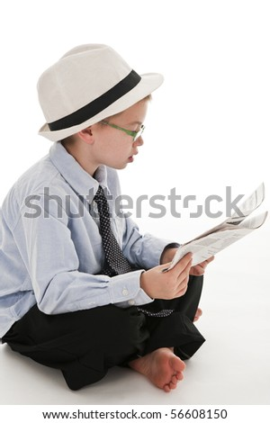 A small boy in the studio, dressed up in a suit and pretending to be a businessman, reading the newspaper. Isolated on white.