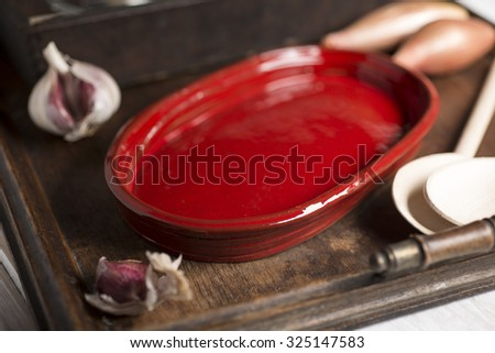 A small, empty, crimson red, rounded rectangular shallow dish alongside wooden spoons and garlic on a wooden tray.
