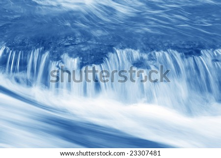 A small falls on a stream in shades of blue.