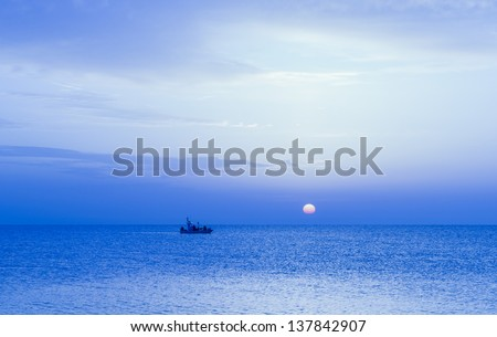 A small fishing boat moves slowly in the Mediterranean Sea under the soft light of the sunset sun.