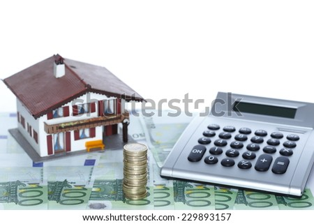 a small house with calculator and money