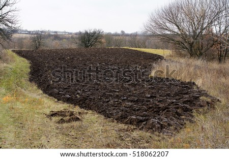 A small picturesque freshly plowed field in November