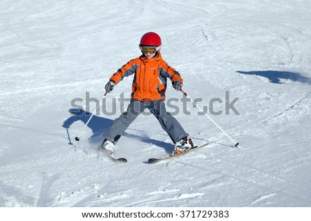 A small skier is training pizza style skiing on piste in winter sunny day