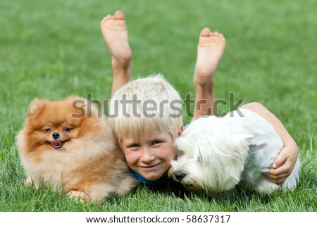 A smiling boy and his pets are lying on the green grass