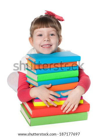A smiling clever little girl is sitting on the floor near the pile of books on the white background