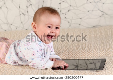 A smiling five-month baby with a tablet computer, at home