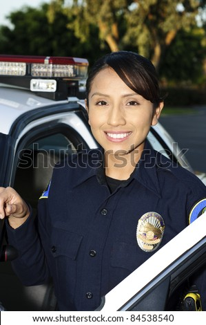 a smiling Hispanic police officer next to her patrol car.
