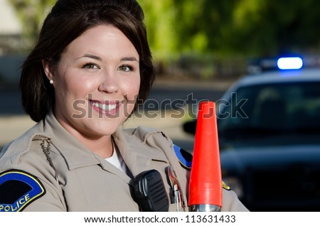 a smiling police officer who is holding her traffic control flashlight.